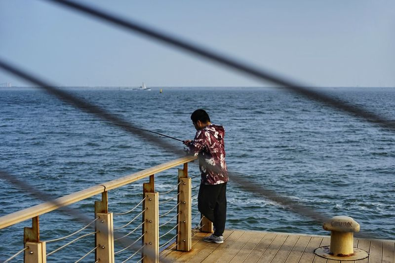 Man fishing while standing on pier sea against sky