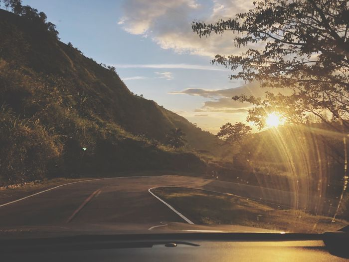 Road seen through car windshield during sunset
