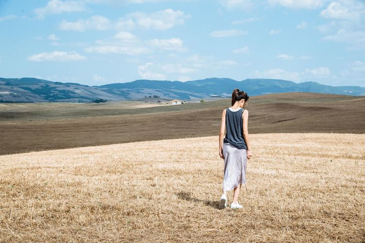 Rear view full length of woman walking on field against mountains