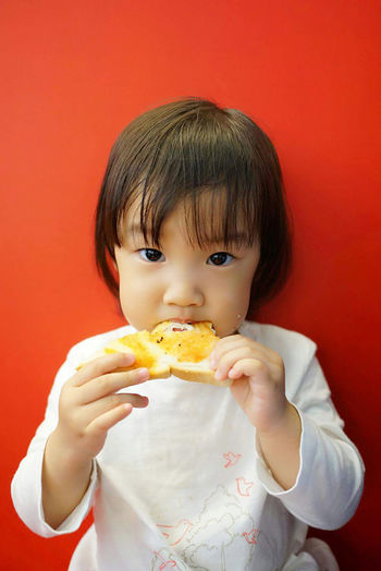 Portrait Of Girl Eating Bread Omelet Against Red Background