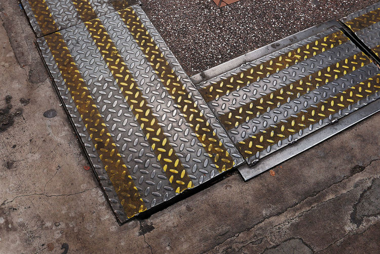 High Angle View Of Sewage Covered With Metal Sheet On Footpath