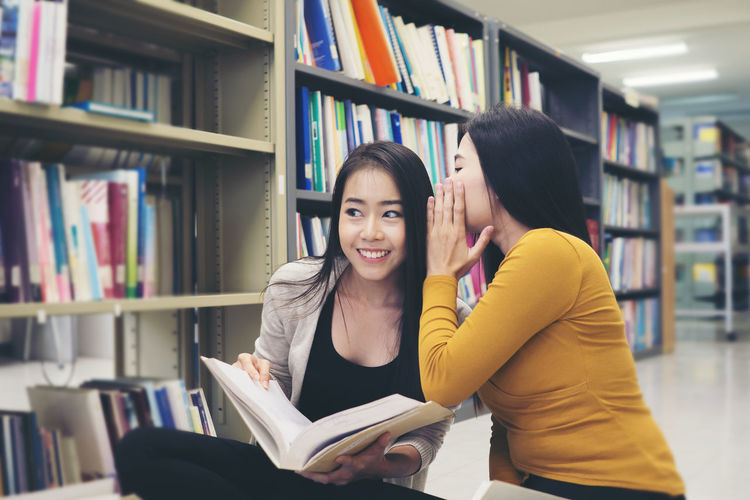 Young woman whispering to female friend studying in library