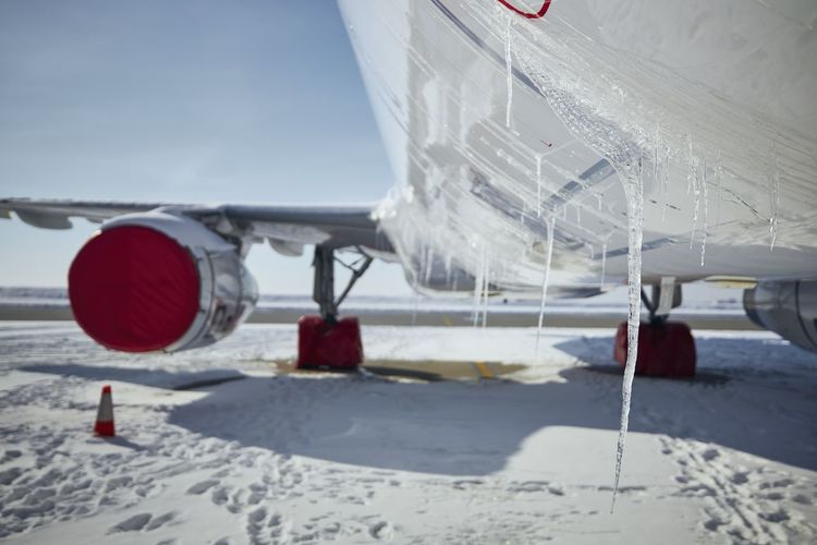 Close-up of airplane at airport during winter