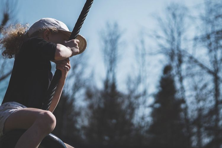 Low angle view of girl swinging on tire swing against sky