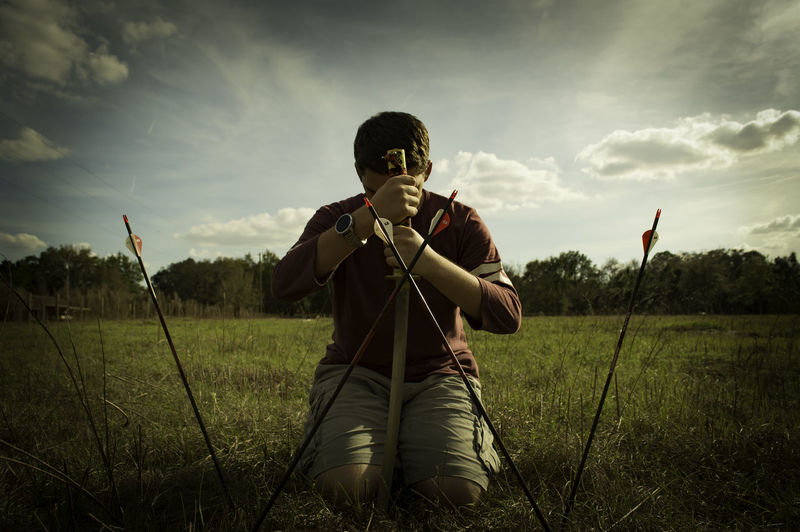 Man Kneeling By Arrows On Field Against Sky