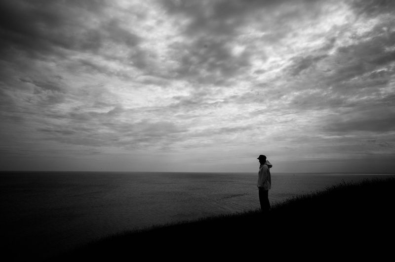 Rear view of silhouette woman photographing sea against sky