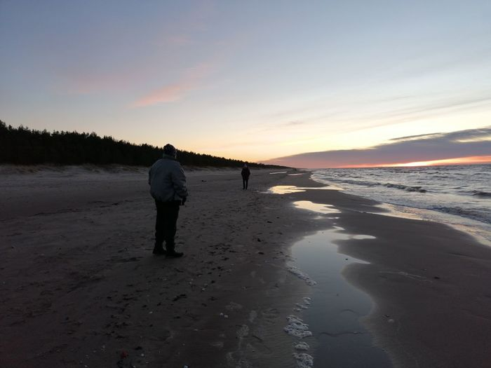 Rear view of people walking on beach during sunset