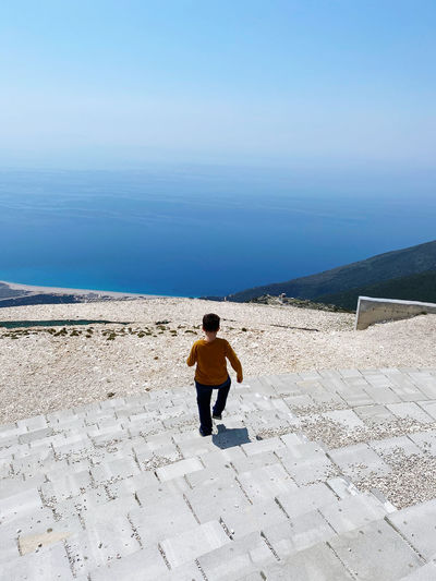 Young boy descenfing scales with mountain sea and sky in background