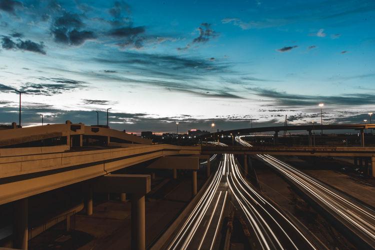 Light Trails On Bridges Against Sky At Dusk