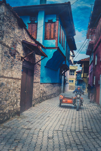 People on the colorful narrow streets in between old historic buildings. Architecture Building Exterior Built Structure Building City Street Outdoors Historical Old Architecture Historic Historical Building Exterior Man Woman Walking Path Colorful Day Village City Town Downtown Urban Perspective