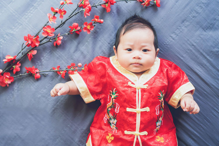 Baby in red dress on blue cloth with flower and looking. Concept Chinese New Year. Asian  Baby Children Family Funny Greeting Happy Holiday Love Lucky New Year Banner Cheerful Child Chinese Congratulation Cute Festival Health Kid Lifestyles Little Model Playing Smile