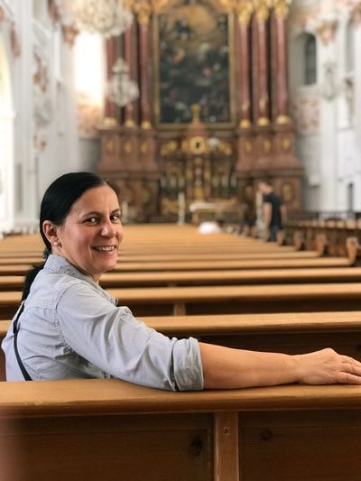 Portrait of smiling woman sitting in pew