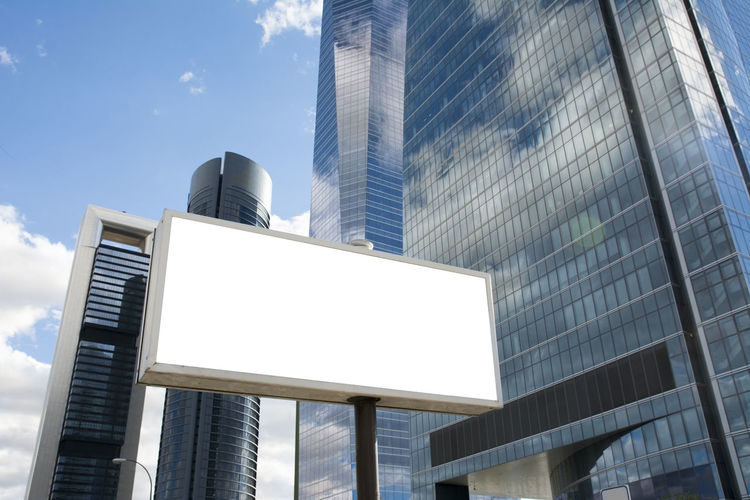 Low angle view of blank billboard against modern buildings in city