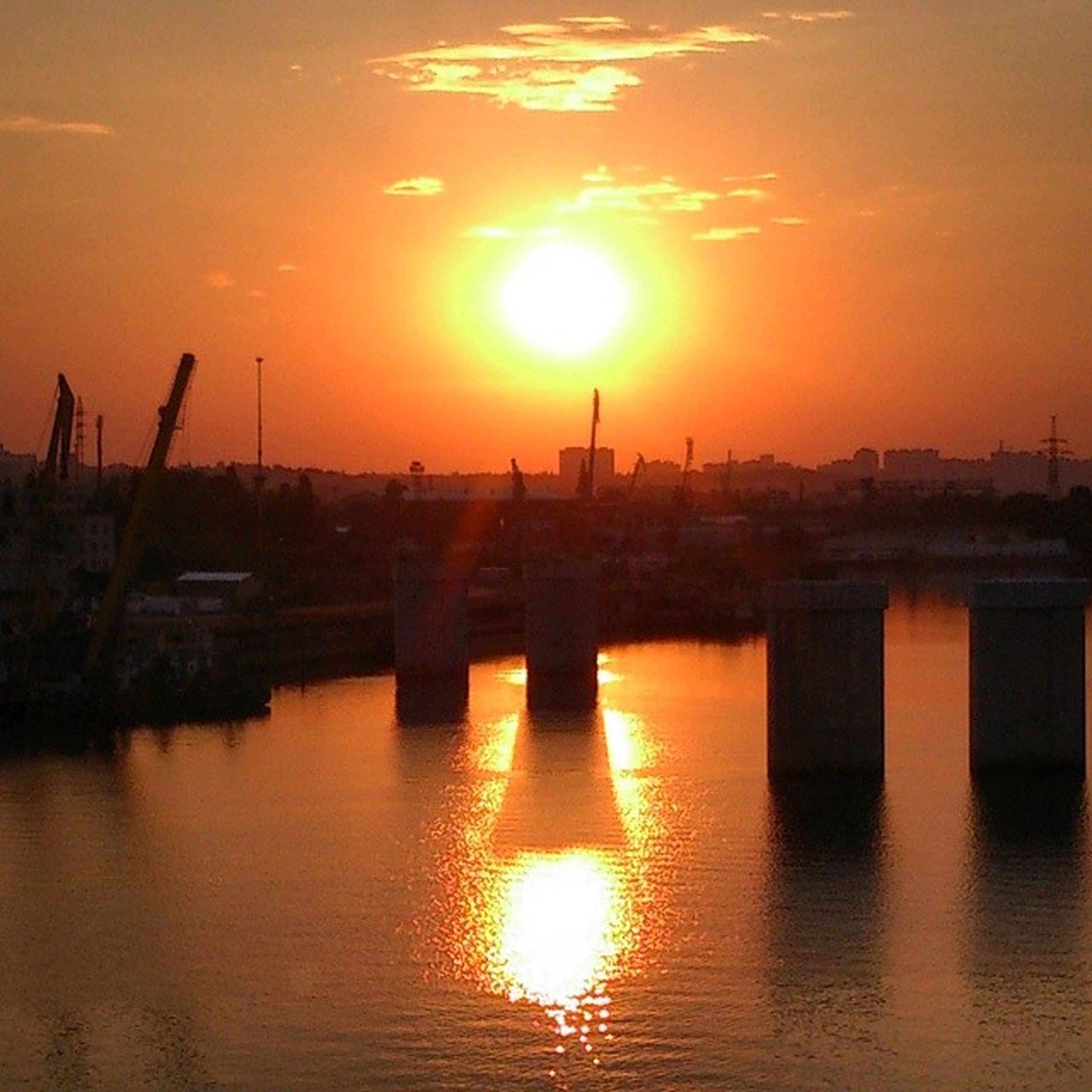 sunset, sun, orange color, water, reflection, silhouette, built structure, waterfront, architecture, sky, sunlight, scenics, beauty in nature, tranquility, idyllic, nature, river, tranquil scene, sea, building exterior