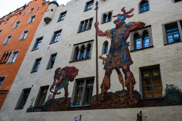 Architecture Art Building Building Exterior Built Structure City Creativity David And Goliath Day Low Angle View Multi Colored No People Outdoors Residential Building Sculpture Sky Statue