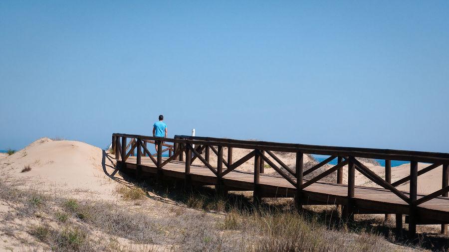 Man standing on bridge against clear blue sky