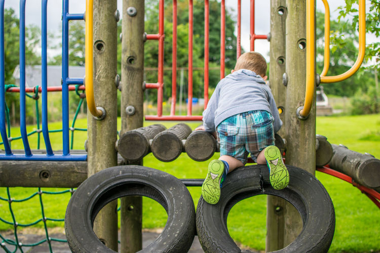 Rear view of boy playing on structure at park