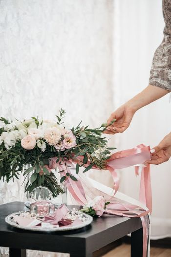 Midsection of touching bouquet during wedding ceremony