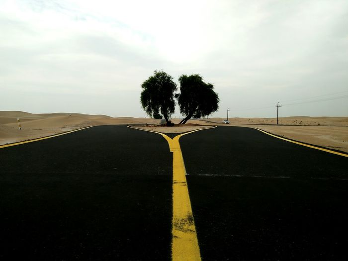 The seprate ways Road Asphalt Tree Outdoors Road Sign Day No People Politics And Government Sky Desert Nature Landscape Illuminated Tranquility Sand