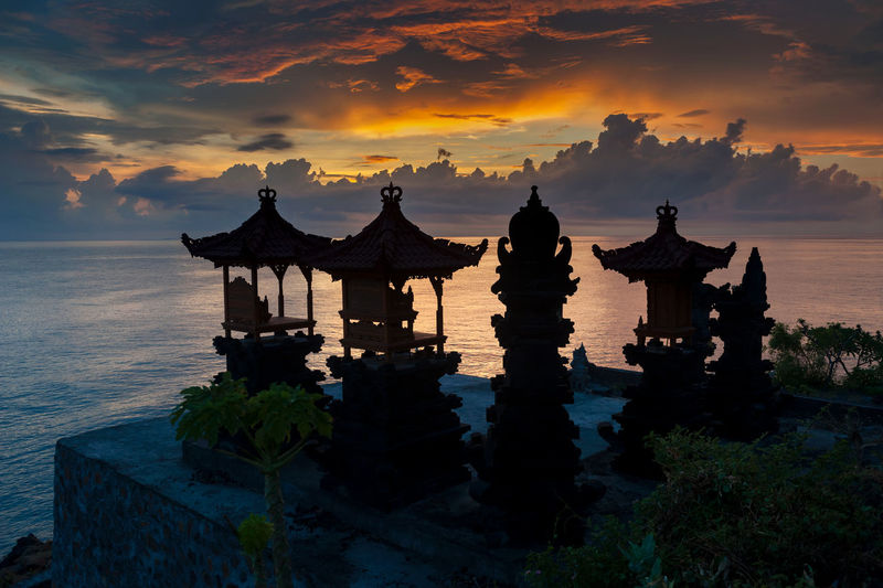 Balinese Hindu Shrines at Sunrise. Silhouetted against the Lombok Strait are several Hindu shrines in the village of Jemeluk, Amed, Bali. Alter Amed ASIA Bali Bali, Indonesia Dawn Hindu Hindu Temple Hinduism Indian Ocean INDONESIA Indonesia_photography Jemeluk Landscape No People Ocean Outdoors Scenics Sky Sunrise Sunrise Silhouette Sunrise_sunsets_aroundworld Tourism Travel Travel Destinations
