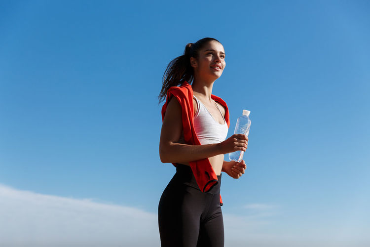 Low angle view of woman jogging against clear sky
