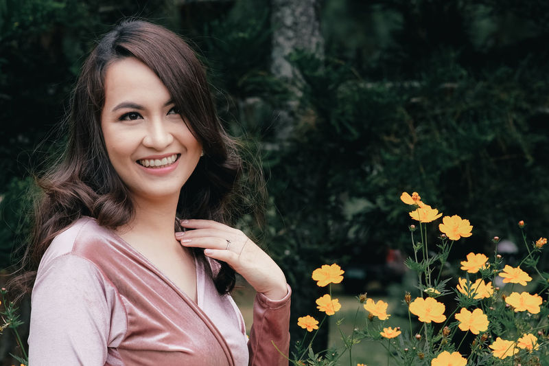 Thoughtful woman smiling while standing by orange flowers outdoors