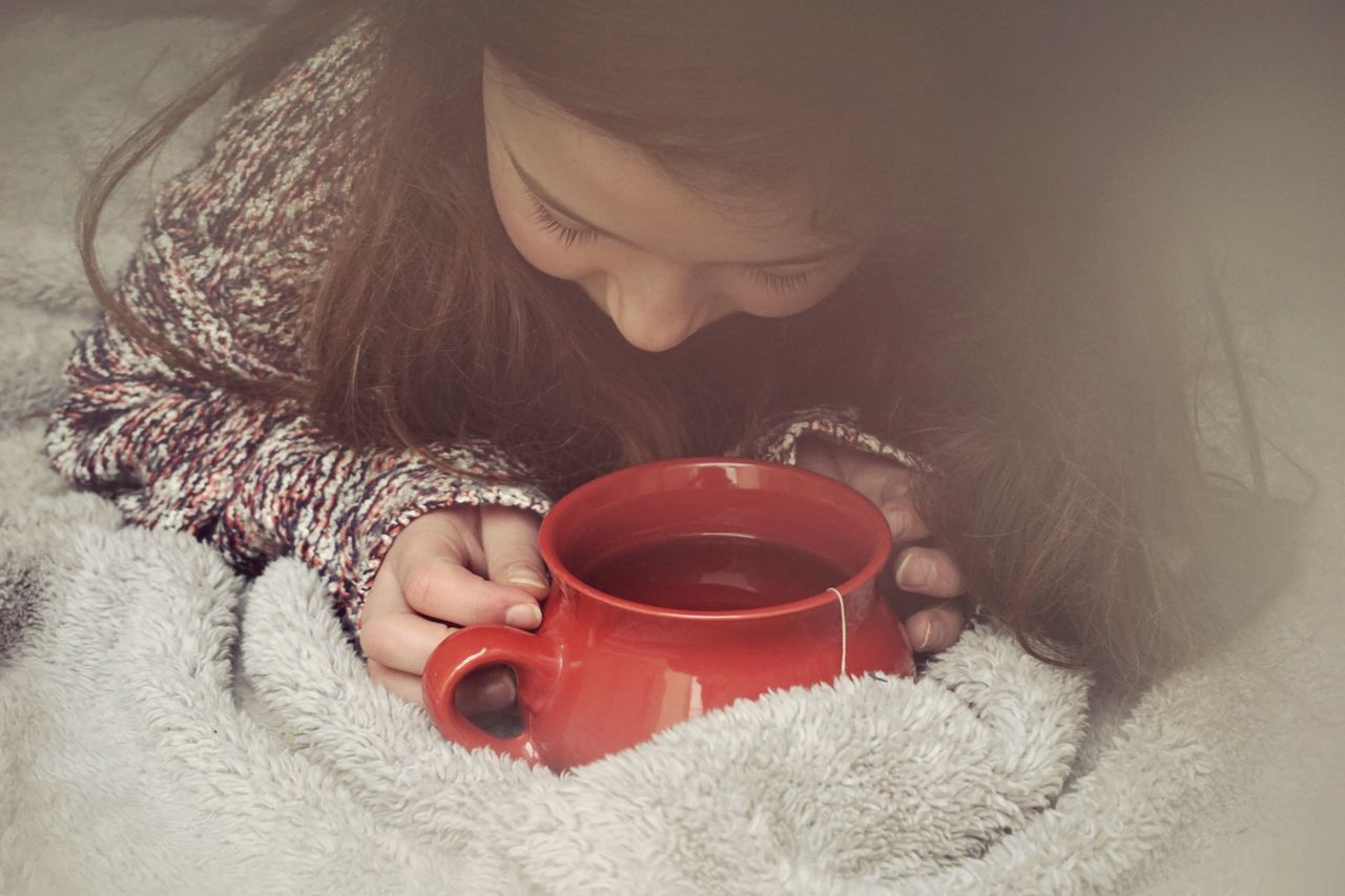 High angle view of girl holding tea cup on blanket