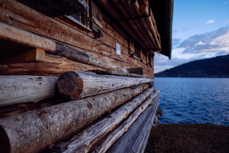 Wooden log at abandoned house in front of lake