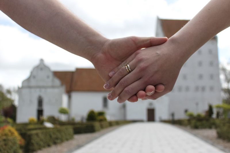 Cropped image of newlywed couple holding hands against church