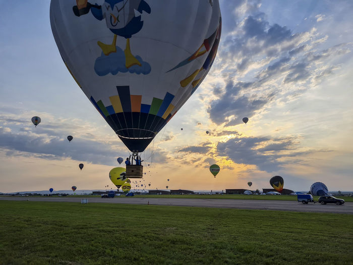 Hot air balloons flying over field against sky during sunset