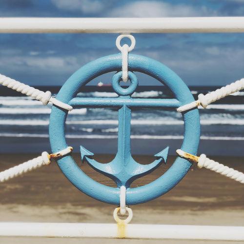 Close-up of blue anchor railing at beach