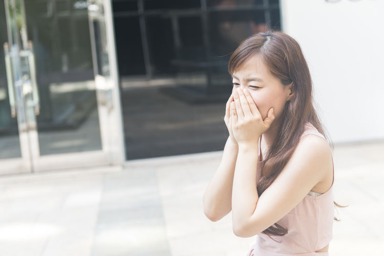 Woman Covering Mouth With Hands While Standing In City