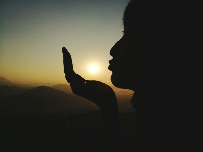Close-up of silhouette hand holding sun against sky during sunset