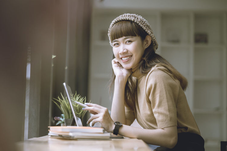Young woman smiling while sitting on table