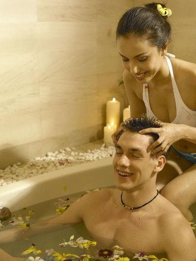 Girlfriend giving head massage to boyfriend in bathtub