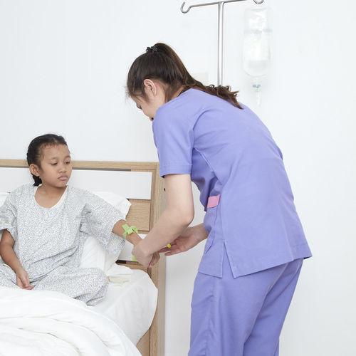 Nurse Examining Girl In Hospital