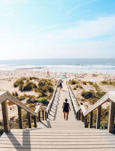 Rear view of woman walking on walkway towards beach
