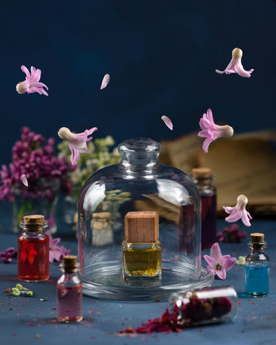 Digital composite image of flowers in mid-air with perfume bottles on table