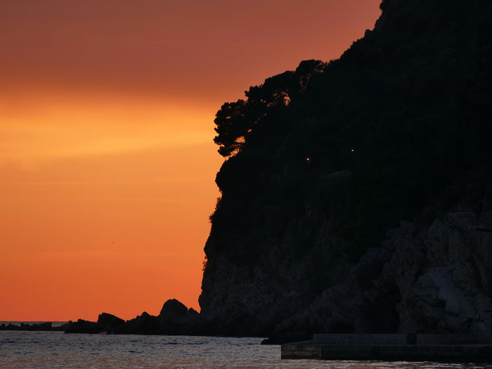 Silhouette rock by sea against sky during sunset