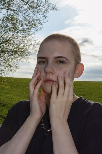 Portrait of beautiful young woman, hands on the face, against sky