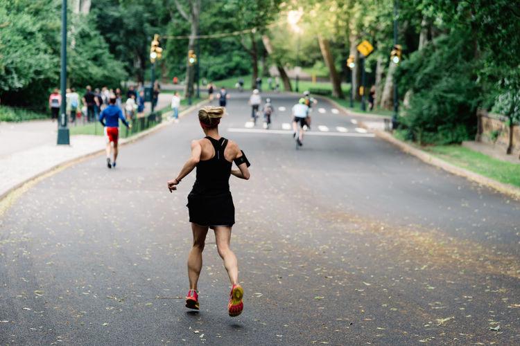 Rear view of marathon runners running on road