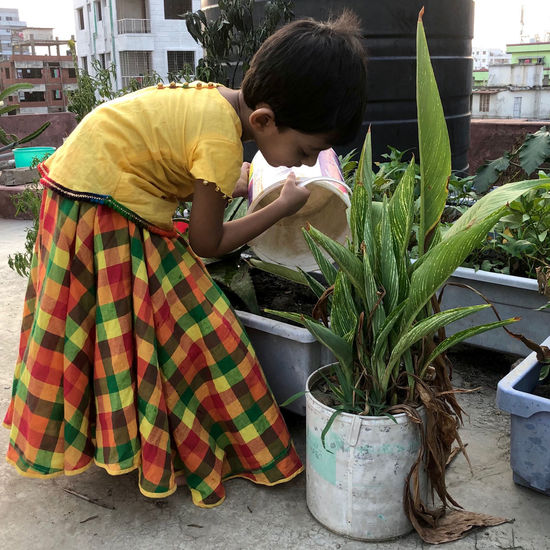 Side view of a girl sitting on potted plant