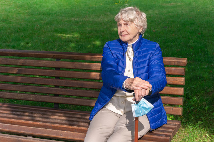 Senior woman looking away while sitting on bench