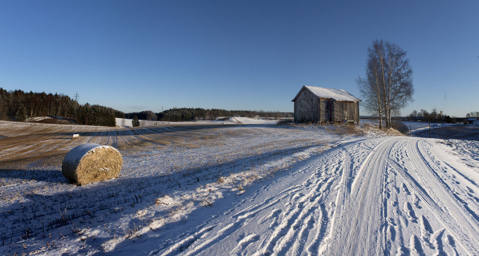 Hay bale and farmhouse in snow covered field