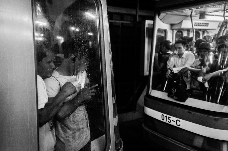 On these tightly packed, over a decade year old coaches, a passenger still finds a way to access messages and listen to music on his mobile phone and just keep it cool. MRT-3 Line that runs from North Avenue in Quezon City to Taft Avenue in Pasay City has a daily passenger capacity of only 350,000, however, the line carries about twice this limit or at least 600,000 passengers per day. | EyeEmBestPics EyeEm Best Shots Eyeem Philippines Philippines Metro Rail Mrt Philippines Train Commuter Train Commuters Traffic Manila Week On Eyeem Documentary Metro Station Mrt The Week On EyeEm Up Close Street Photography