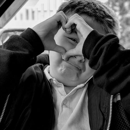Portrait of cute boy making heart shape