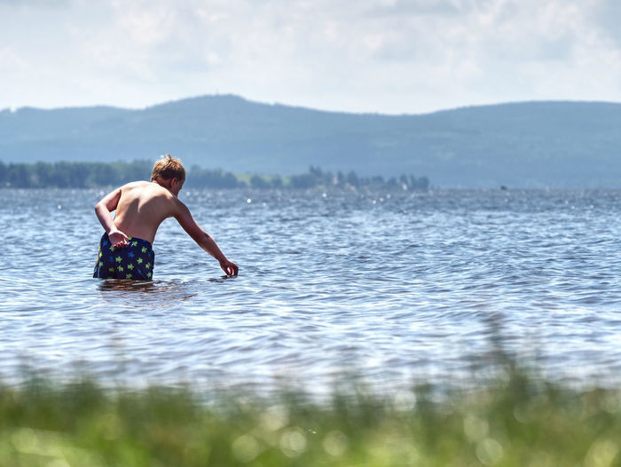 Boy stay in cold lake with water under knee and test temperature. cold spring day for swim.