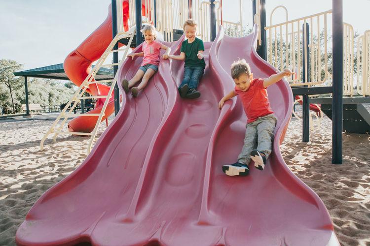 Playful children sliding in playground