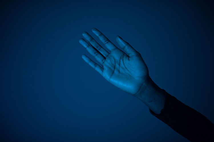 Close-up of hand gesturing against blue background