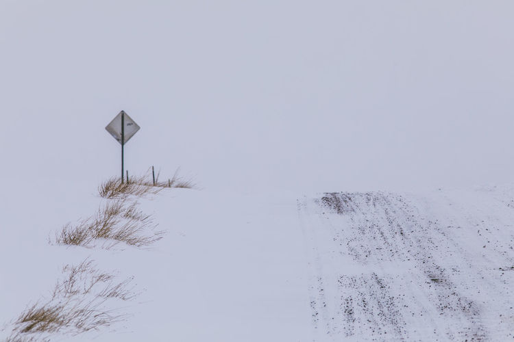 Cold Temperature Winter Snow Sky No People Beauty In Nature Nature Sign Day Covering Road Tranquility Communication White Color Tranquil Scene Road Sign Copy Space Environment Scenics - Nature Outdoors Snowing Snowcapped Mountain